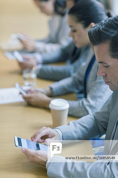 Geschäftsmann mit Handy im Konferenzraum