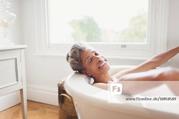 Smiling mature woman with eyes closed enjoying bath