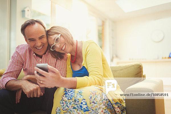 Lächelndes reifes Paar SMS mit Handy im Wohnzimmer