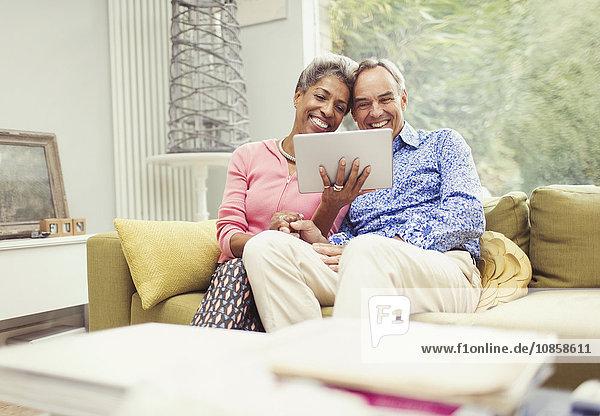 Lächelndes reifes Paar mit digitalem Tablett auf dem Wohnzimmersofa