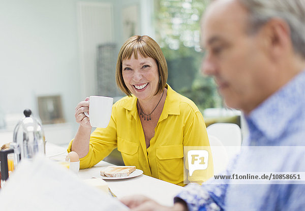 Portrait lächelnde reife Frau beim Kaffeetrinken am Frühstückstisch