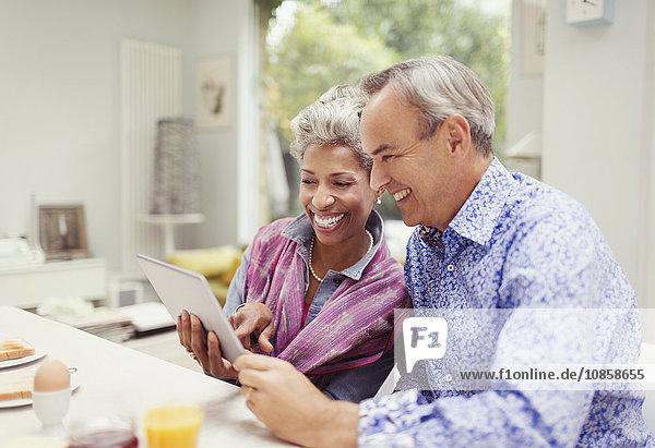Lächelndes reifes Paar  das sich ein digitales Tablett am Frühstückstisch teilt.