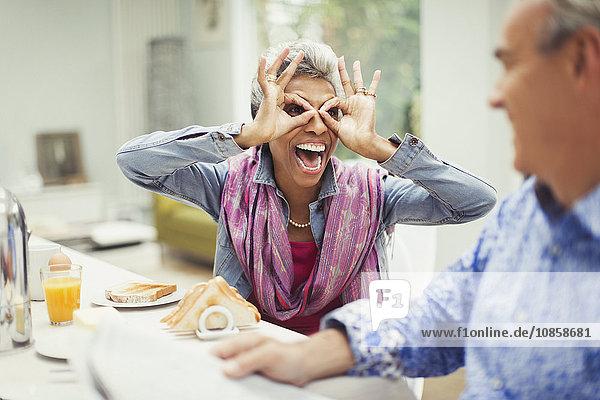 Verspielte reife Frau mit Fingerbrille am Frühstückstisch