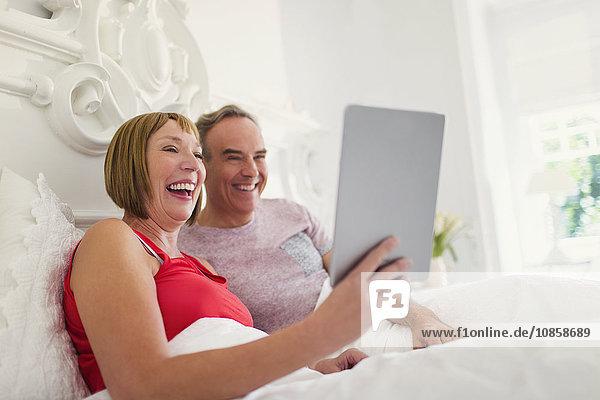 Lachendes reifes Paar mit digitalem Tablett im Bett