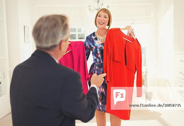 Ehemann hilft Frau entscheiden  welches Kleid sie tragen soll