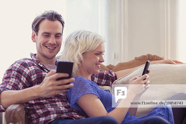 Paar SMS mit Handys auf dem Wohnzimmersofa