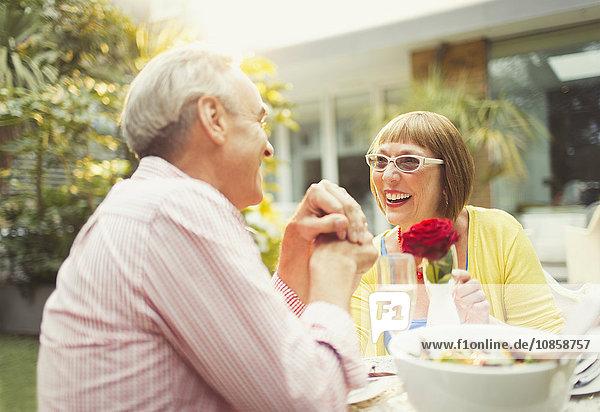 Lächelndes reifes Paar beim Mittagessen im Garten