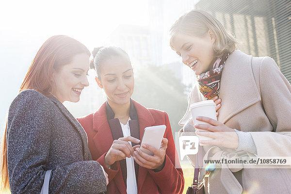 Frauen beim SMSen und Kaffeetrinken im Freien