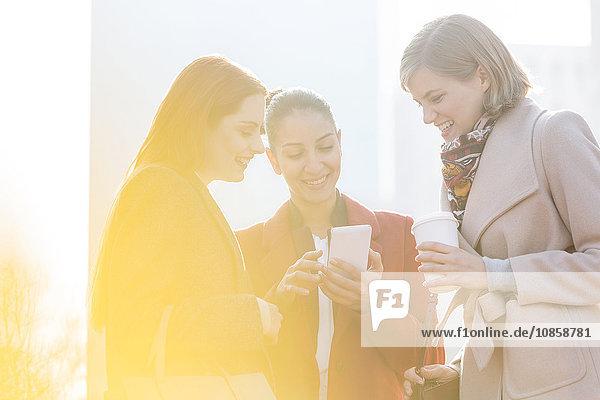 Lächelnde Geschäftsfrauen beim SMSen und Kaffeetrinken im Freien