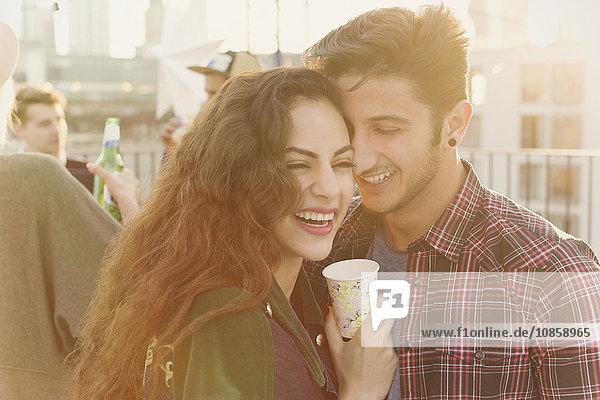 Lachendes junges Paar umarmt sich auf der Dachparty