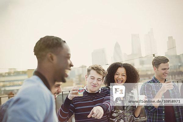 Junge erwachsene Freunde beim Trinken und Lachen auf der Dachparty