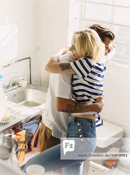 Junge Paare umarmen sich in der Wohnküche