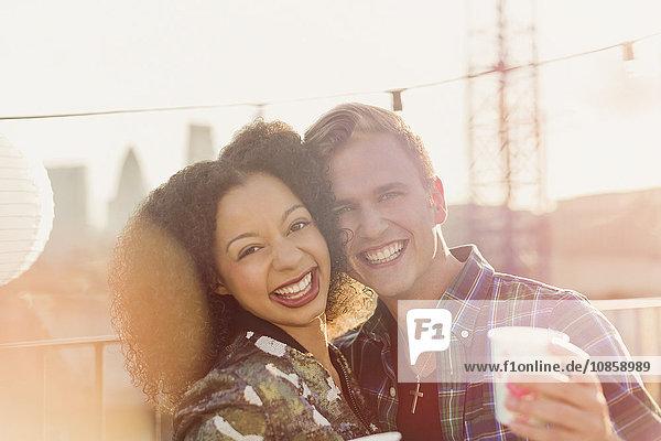 Portrait lächelndes junges Paar genießt Dachparty