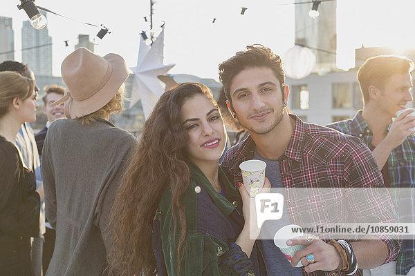 Portrait lächelndes junges Paar beim Trinken auf der Dachparty