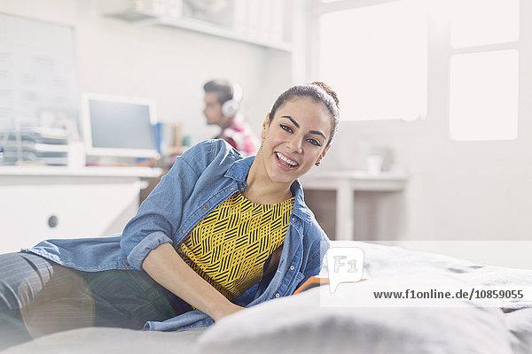 Portrait lächelnde junge erwachsene Frau beim Lesen im Bett