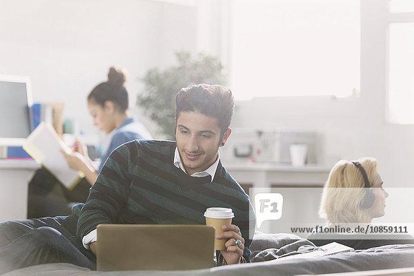 Männlicher Student trinkt Kaffee am Laptop