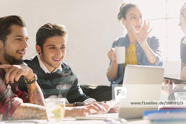 Kreative junge Geschäftsleute  die am Laptop arbeiten