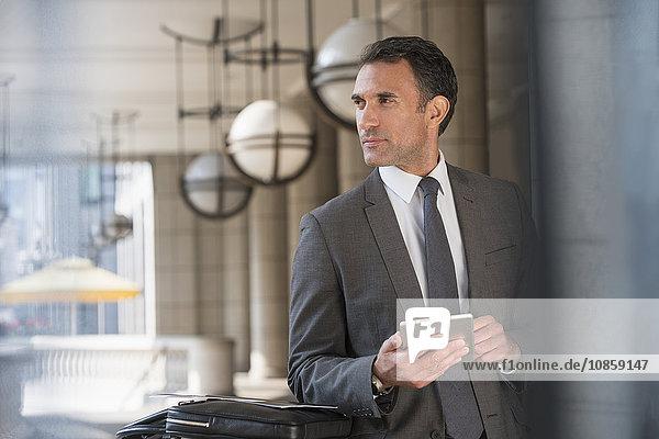 Geschäftsmann mit digitalem Tablett im Hintergrund