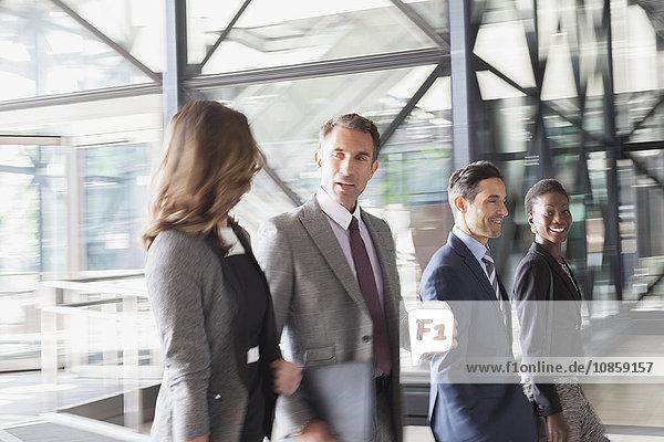 Geschäftsleute sprechen und betreten moderne Bürolobby