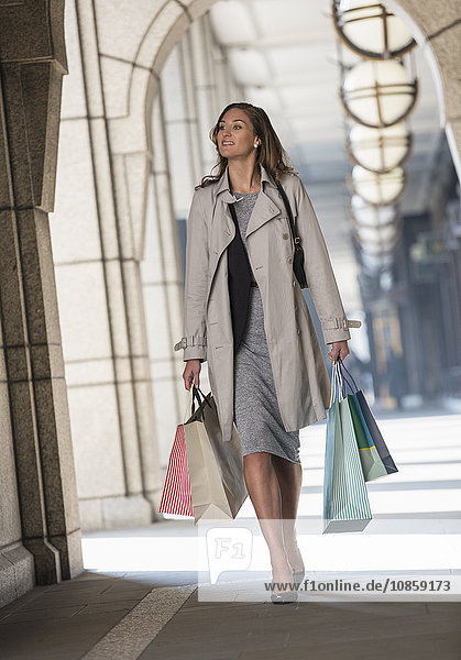 Businesswoman carrying shopping bags in cloister