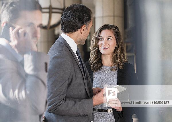 Geschäftsmann und Geschäftsfrau mit digitalem Tablettgespräch