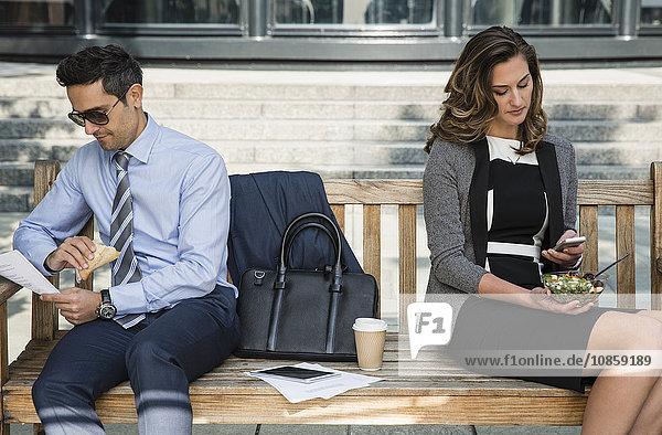 Geschäftsmann und Geschäftsmann  der auf der Bank arbeitet und zu Mittag isst.