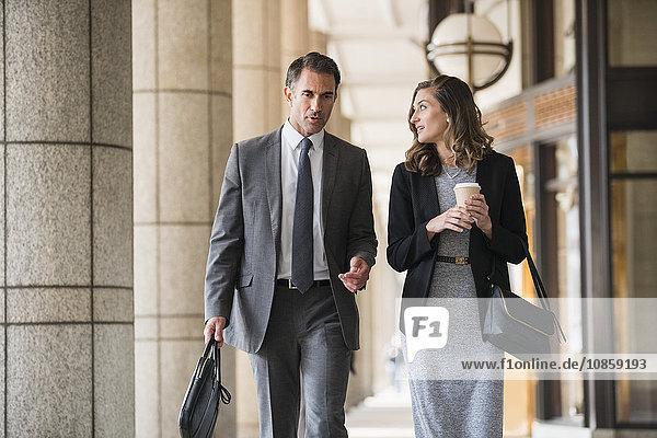 Firmenkaufmann und Geschäftsfrau mit Kaffee im Kreuzgang