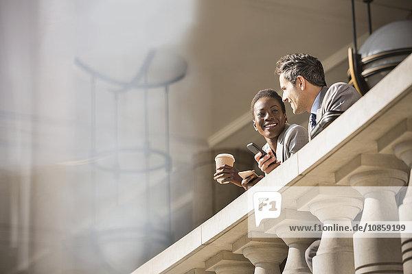 Geschäftsmann und Geschäftsfrau beim Kaffeetrinken am Geländer