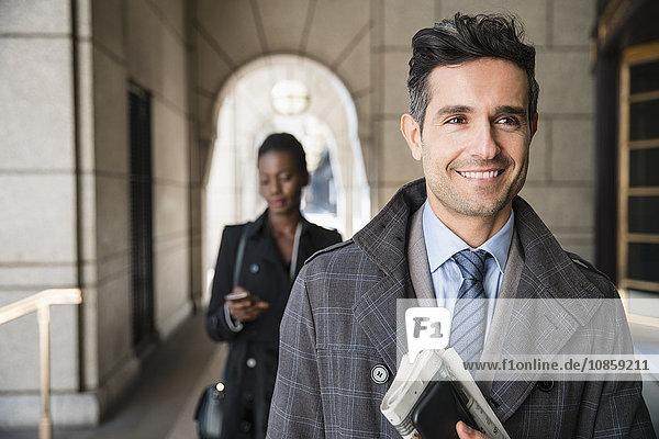 Lächelnder Geschäftsmann mit Zeitung und Handy im Kreuzgang