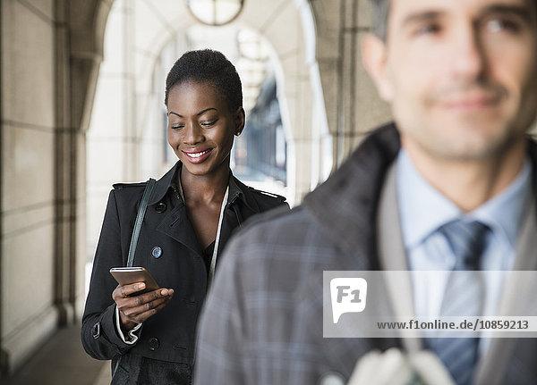 Geschäftsfrau SMS mit Handy im Kloster