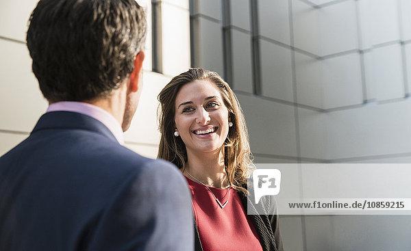 Corporate Geschäftsfrau lächelt und spricht mit Geschäftsmann