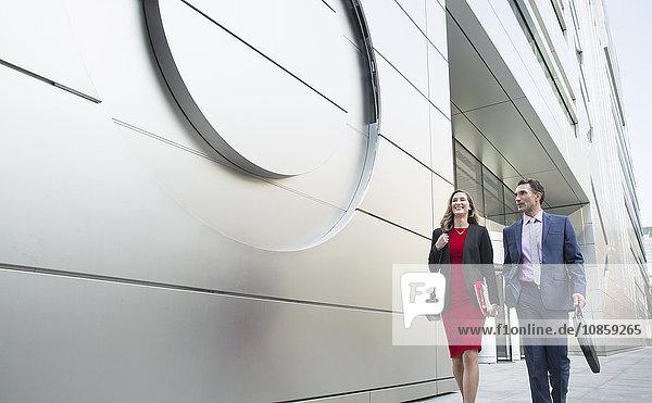 Geschäftsmann und Geschäftsfrau  die vor dem modernen Gebäude spazieren gehen.