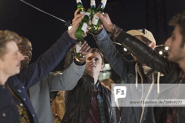 Junge Männer toasten Bierflaschen auf der Party