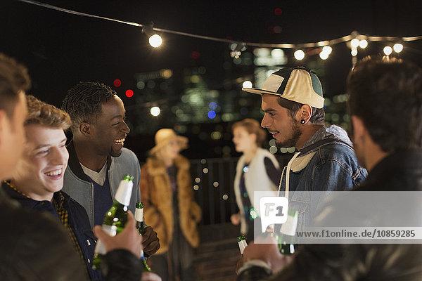 Junge Freunde beim Reden und Trinken auf der Dachparty
