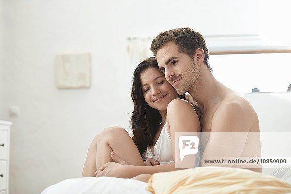 Junges Paar sitzt im Bett