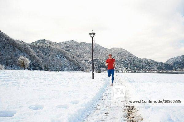 Männlicher Läufer läuft auf schneebedeckten Wegen  Kawaguchiko-See  Berg Fuji  Japan