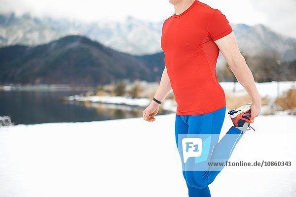 Seitenansicht eines männlichen Läufers,  der sein Bein am schneebedeckten Seeufer streckt,  Kawaguchiko-See,  Berg Fuji,  Japan