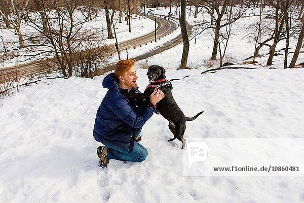 Junger Mann streichelt Hund im verschneiten Central Park  New York  USA