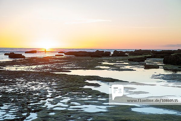 Distant view of woman at sunset on rocky beach  Cape of Trafalgar  Spain