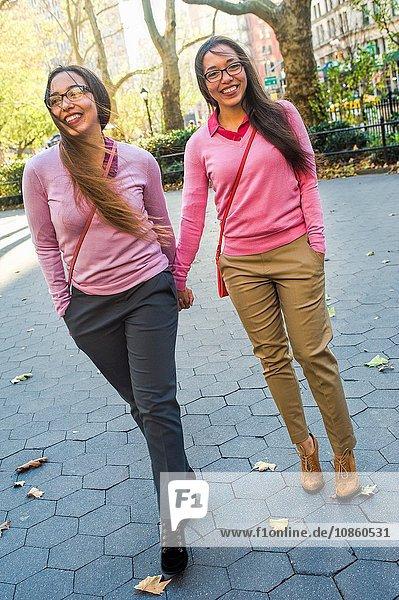 Zwillingsschwestern halten sich an den Händen und gehen auf der Straße