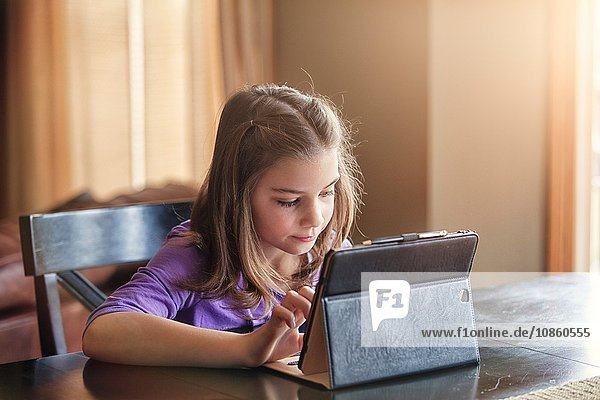 Girl using wireless digital tablet at home