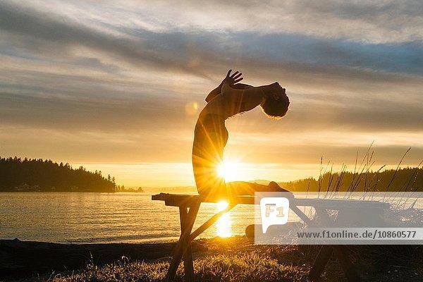 Woman practising yoga by lake at sunset