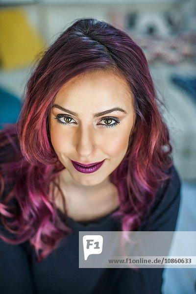 Porträt einer jungen Frau mit rosa Haaren  lächelnd