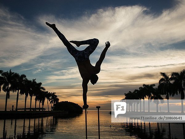 Mature man balancing on pole in water  dusk  South Pointe Park  South Beach  Miami  Florida  USA
