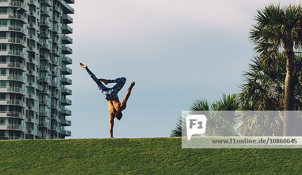 Mature man doing one handed handstand on grass  South Pointe Park  South Beach  Miami  Florida  USA