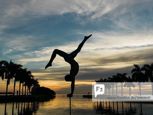 Mature man balancing on pole  dusk  South Pointe Park  South Beach  Miami  Florida  USA