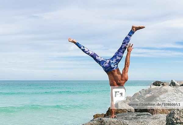 Mature man doing one handed handstand on rock  South Pointe Park  South Beach  Miami  Florida  USA