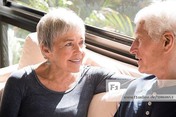 Älteres Ehepaar  entspannend  von Angesicht zu Angesicht sitzend