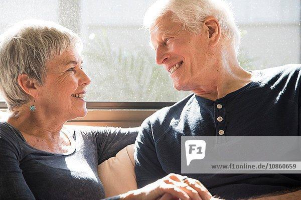 Älteres Ehepaar sitzt zusammen  von Angesicht zu Angesicht  lächelnd