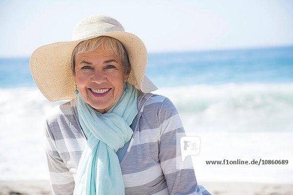 Porträt einer älteren Frau  die sich am Strand entspannt und lächelt